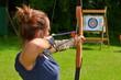 Leinwanddruck Bild - Junge Frau beim Bogenschiessen