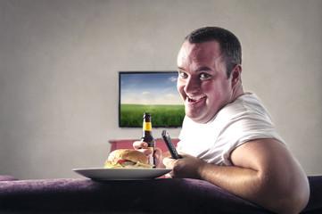 men enjoying his meal while watching tv