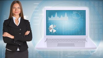 Businesswoman standing with open laptop