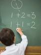 Cute pupil writing maths on chalkboard