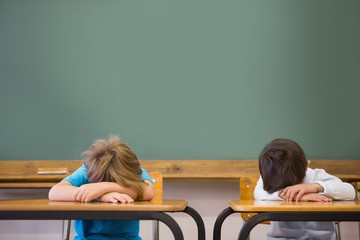 Sleepy pupils napping at desks in classroom