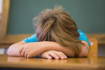 Sleepy pupil napping at desk in classroom