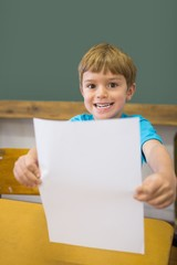 Cute pupil smiling at camera in classroom showing page