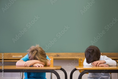 canvas print picture Sleepy pupils napping at desks in classroom