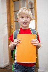 Cute pupil smiling at camera in classroom holding notepad