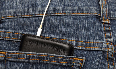 mobile phone in the pocket of jeans with headphones connected