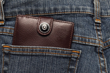 brown leather wallet in the pocket of jeans