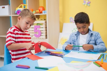 Cute little boys drawing at desk