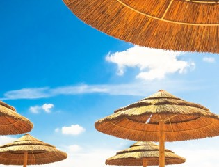Beach umbrellas on blue sky background with clouds