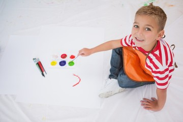 Cute little boy painting on floor in classroom