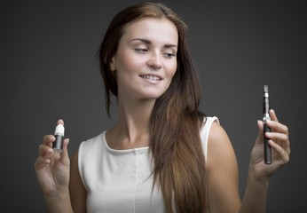 Woman holding e-cigarette and bottle of liquid