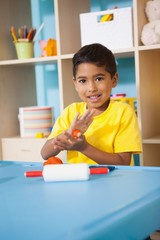 Cute little boy playing with modelling clay in classroom