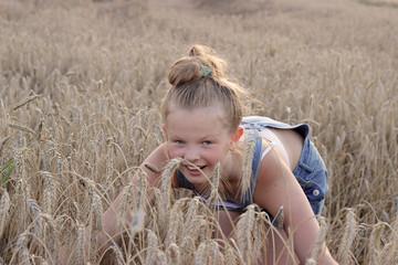 Wesoła dziewczynka na polu zboża