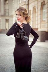Street portrait of beautiful woman in black dress with red lips