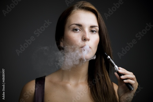 Elegant woman smoking e-cigarette with smoke - 68680497