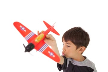 Happy little boy playing with toy airplane