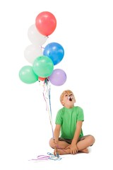 Happy little boy in tiger face paint with balloons