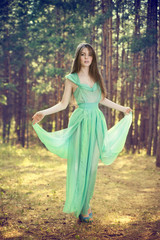 Beautiful young woman in a turquoise dress in a pine forest