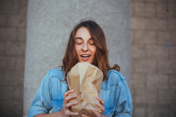 portrait of a cute girl smelling a package with fresh buns
