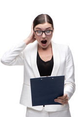 Surprised young business woman looking at folder wonderingly