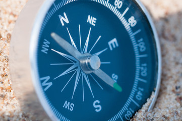 Compass on the sea sand. Close up.
