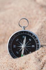 Compass on the sea sand.
