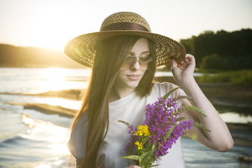Portrait of a beautiful woman in a hat  of a sunset