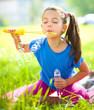Little girl is blowing a soap bubbles