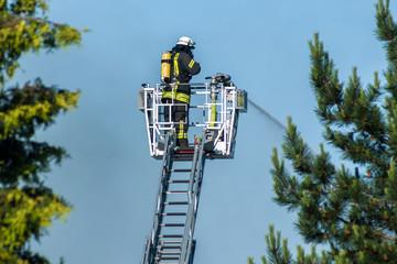 Feuerwehrmann beim Feuerlöschen von der großen Leiter aus