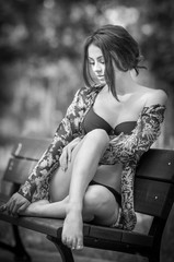 Attractive girl in swimsuit sitting relaxed on a bench