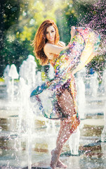 Attractive girl in multicolored short dress playing with water