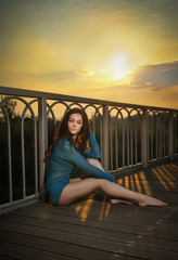 Fashionable redhead in blue blouse and long legs laying down