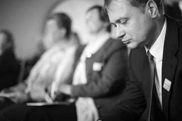 Profile of a businessman at conference; monochrome