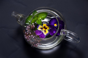 Herbal tea with flowers. Tea with mint, oregano and viola.