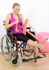 Frau im Rollstuhl trainiert mit Theraband