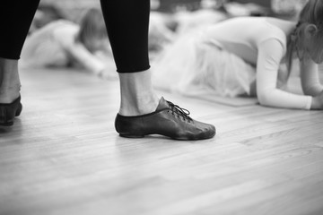 Feet of trainer in ballet school for small girs