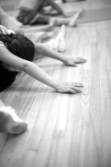 Girls stretching on the floor; monochrome