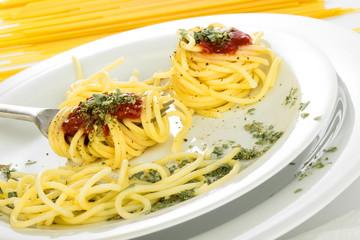 Spaghetti auf weißem Teller und Rohnudeln