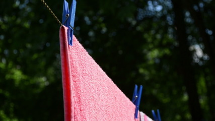 hand put pins clips on drying laundry hang on clothesline