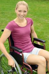 Twen sitzt in Rollstuhl und lächelt