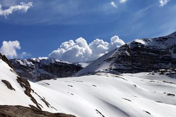 Snow rocks and cloudy blue sky