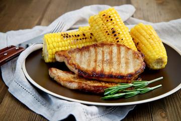 Grilled pork steak with corn on wooden background