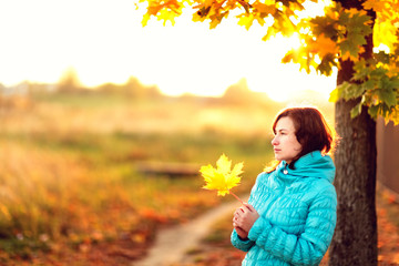 Young woman standing below autumn tree on sunset