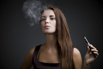 Elegant woman smoking e-cigarette with smoke