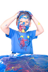 kleiner Junge bemalt sich selbst mit Blauer Farbe