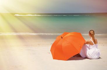 Girl with an orange umbrella on the sandy beach