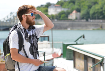 Lost bearded male tourist holding a map and gesturing with hands