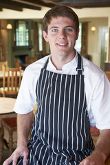 Chef Wearing Whites And Apron Sitting In Restaurant