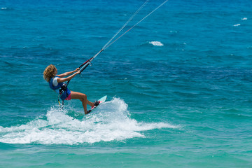 A young woman kite-surfer rides in greenish-blue sea
