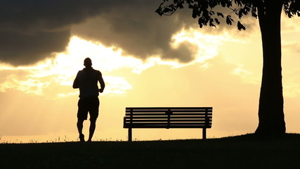 Silhouette man jogging up to a bench at sunset
